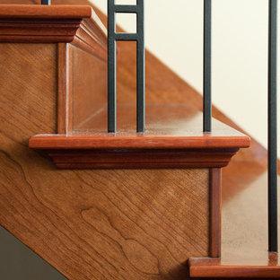 Diseño de escalera de estilo americano con escalones de madera, contrahuellas de madera y barandilla de varios materiales