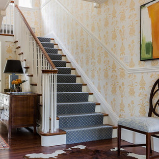 Elegant wooden u-shaped staircase photo in Boston with painted risers