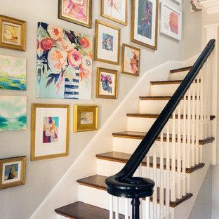 """Esempio di una scala a """"L"""" tradizionale di medie dimensioni con pedata in legno, alzata in legno verniciato e parapetto in legno"""