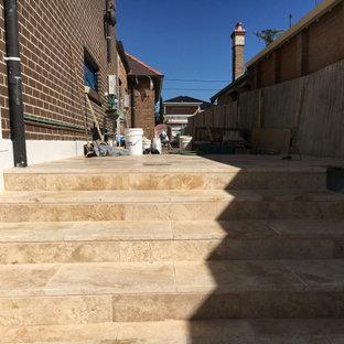 Imagen de escalera recta, moderna, pequeña, con escalones de travertino y contrahuellas de travertino