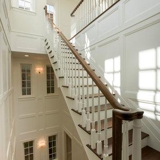 シカゴの広い木のトランジショナルスタイルのおしゃれな折り返し階段 (フローリングの蹴込み板、木材の手すり) の写真