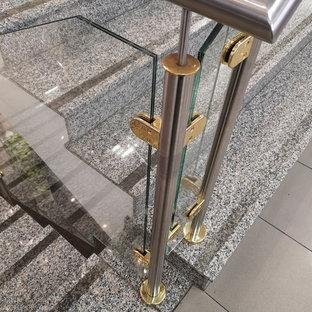 Immagine di una piccola scala a rampa dritta minimalista con pedata in vetro, alzata in metallo e parapetto in metallo