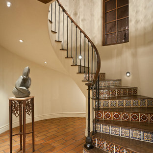 Tuscan wooden curved metal railing staircase photo in Phoenix with tile risers