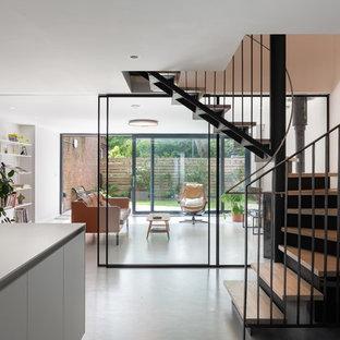 Idéer för en mellanstor modern svängd trappa i trä, med sättsteg i metall och räcke i metall