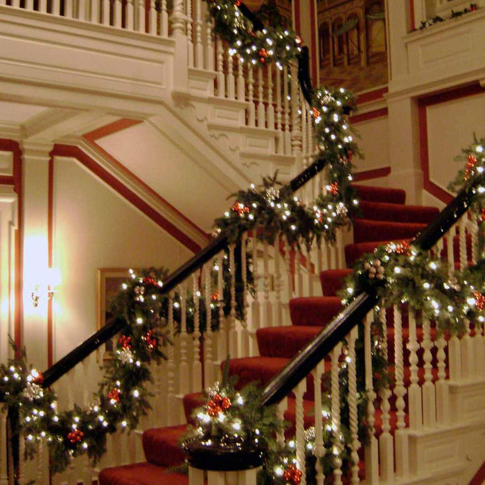 Holiday Decorations we set  up this staircase in Greenwich, CT. Pine Cones and red balls to tie in with the carpet of the stairs.