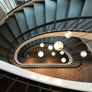 Idee per un'ampia scala a chiocciola contemporanea con pedata in legno verniciato, alzata in legno verniciato e parapetto in metallo