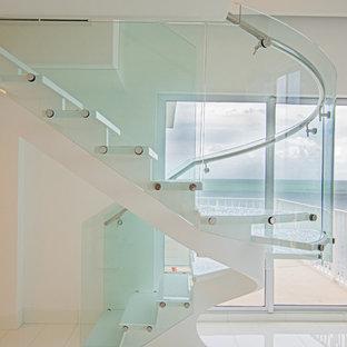 """Ispirazione per una scala a """"U"""" costiera di medie dimensioni con pedata in vetro, nessuna alzata e parapetto in vetro"""