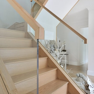 Example of a mid-sized classic wooden curved wood railing staircase design in Other with glass risers