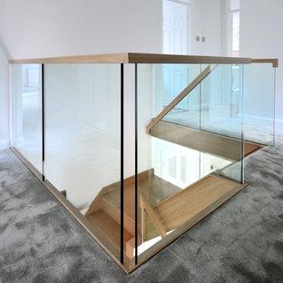 バッキンガムシャーの中サイズの木のトラディショナルスタイルのおしゃれなサーキュラー階段 (ガラスの蹴込み板、木材の手すり) の写真