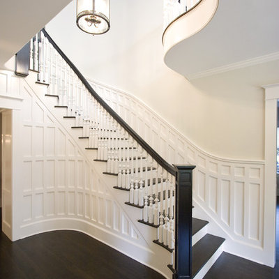Example of a large classic wooden curved wood railing staircase design in New York with painted risers