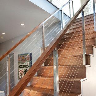 中サイズの木のモダンスタイルのおしゃれな直階段 (ワイヤーの手すり、木の蹴込み板) の写真