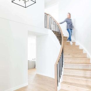 カルガリーの大きい木のトランジショナルスタイルのおしゃれならせん階段 (木の蹴込み板、混合材の手すり) の写真