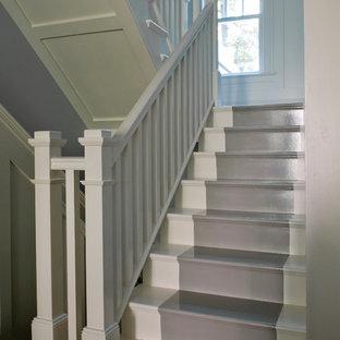 На фото: п-образная лестница среднего размера в морском стиле с деревянными ступенями, деревянными подступенками, деревянными перилами и панелями на стенах с