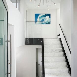 Foto de escalera recta, costera, grande, con escalones de mármol, contrahuellas de mármol y barandilla de vidrio