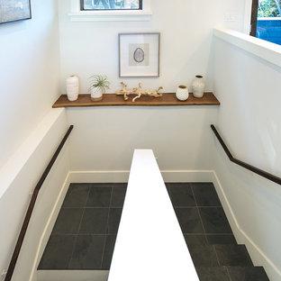 На фото: п-образная лестница среднего размера в морском стиле с ступенями из сланца, деревянными подступенками и деревянными перилами