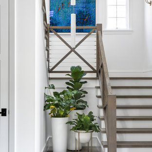 Inspiration for a medium sized coastal wood u-shaped wire cable railing staircase in Orange County with painted wood risers.
