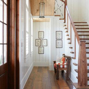 Идея дизайна: п-образная лестница в морском стиле с деревянными ступенями, деревянными перилами и крашенными деревянными подступенками