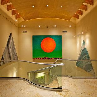 Ejemplo de escalera de caracol, minimalista, grande, sin contrahuella, con escalones de madera y barandilla de vidrio