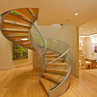 Idee per una grande scala a chiocciola moderna con pedata in legno, nessuna alzata e parapetto in vetro
