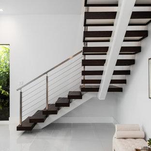 Diseño de escalera suspendida, moderna, de tamaño medio, sin contrahuella, con escalones de madera pintada y barandilla de metal