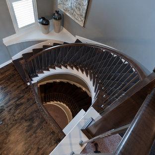 カンザスシティの中サイズの木のトランジショナルスタイルのおしゃれなサーキュラー階段 (木の蹴込み板、木材の手すり) の写真