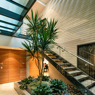 Large midcentury modern concrete u-shaped open and glass railing staircase photo in Los Angeles