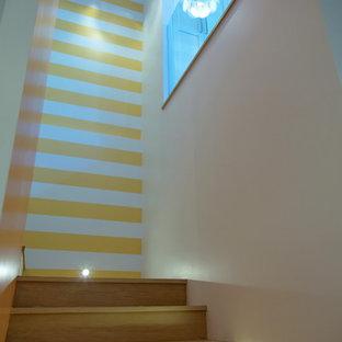 Ejemplo de escalera en U, clásica renovada, con escalones de madera y contrahuellas de madera
