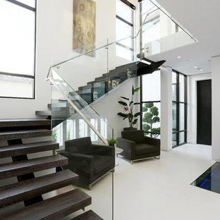 """Foto di una grande scala a """"L"""" contemporanea con pedata in legno, nessuna alzata e parapetto in vetro"""