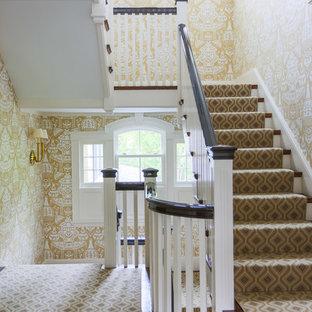 ボストンの木のトラディショナルスタイルのおしゃれな折り返し階段 (木材の手すり、フローリングの蹴込み板) の写真