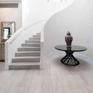 Large trendy marble curved staircase photo in Miami with marble risers