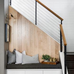 Aménagement d'un escalier contemporain en L de taille moyenne avec des marches en bois, des contremarches en bois, un garde-corps en câble et du lambris.
