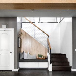 Diseño de escalera en L y panelado, actual, de tamaño medio, con escalones de madera, contrahuellas de madera, barandilla de cable y panelado