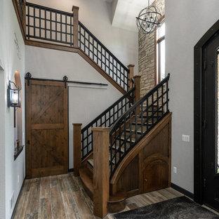 Ejemplo de escalera en U, rústica, grande, con escalones de madera, contrahuellas de madera y barandilla de metal