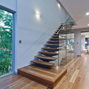 Inspiration for a mid-sized contemporary wooden straight glass railing staircase remodel in Perth with glass risers