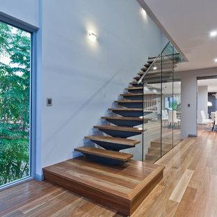 Новый формат декора квартиры: прямая лестница среднего размера в современном стиле с деревянными ступенями, стеклянными подступенками и стеклянными перилами