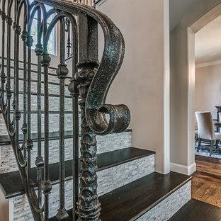 Imagen de escalera en L, clásica, grande, con escalones de madera, contrahuellas de travertino y barandilla de metal