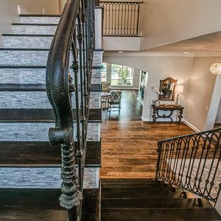 Imagen de escalera en L, tradicional renovada, grande, con escalones de madera, contrahuellas de travertino y barandilla de metal