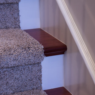 Ejemplo de escalera en U, tradicional, de tamaño medio, con escalones enmoquetados, contrahuellas enmoquetadas y barandilla de varios materiales