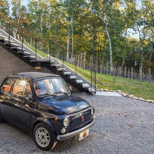 На фото: большая лестница на больцах в современном стиле с ступенями из сланца и перилами из тросов без подступенок с