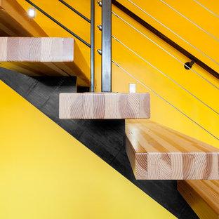 Industriell inredning av en rak trappa i trä, med öppna sättsteg och kabelräcke