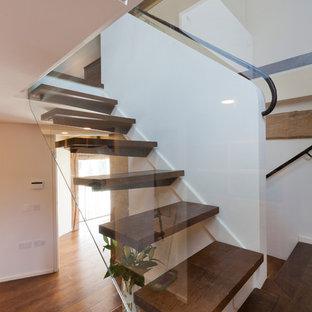 Foto di una scala sospesa design con pedata in legno e nessuna alzata