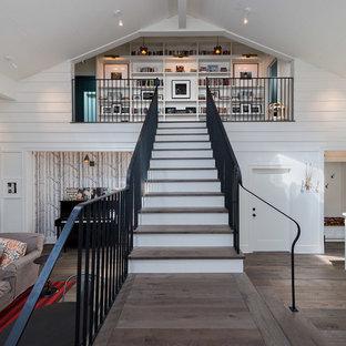 На фото: большая прямая лестница в современном стиле с деревянными ступенями, деревянными подступенками и металлическими перилами с