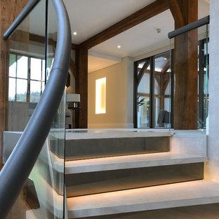他の地域の巨大なライムストーンのコンテンポラリースタイルのおしゃれならせん階段 (ライムストーンの蹴込み板、ガラスの手すり) の写真