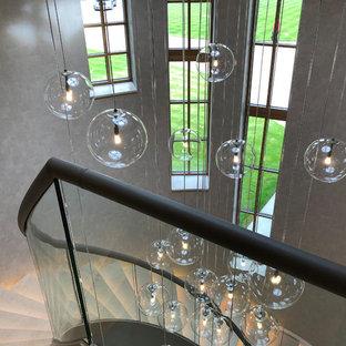 Foto di un'ampia scala a chiocciola design con pedata in pietra calcarea, alzata in pietra calcarea e parapetto in vetro