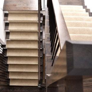 Ejemplo de escalera en U, de estilo americano, grande, con escalones de madera, contrahuellas de madera pintada y barandilla de varios materiales