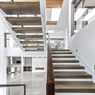 Large trendy wooden u-shaped open and glass railing staircase photo in Seattle
