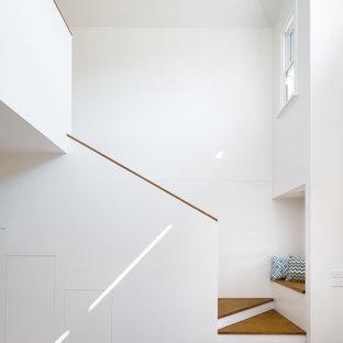 Esempio di una scala moderna con pedata in legno, alzata in legno verniciato e parapetto in legno