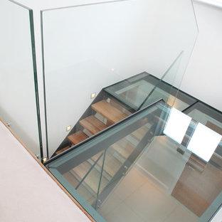 Foto de escalera en U, actual, de tamaño medio, con escalones de madera y contrahuellas de vidrio