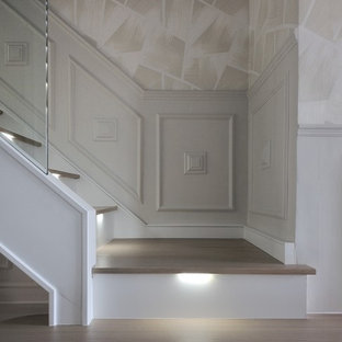 Staircase - large contemporary wooden curved glass railing staircase idea in London with glass risers