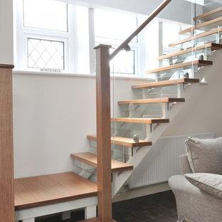 """Immagine di una scala a """"L"""" minimal di medie dimensioni con pedata in legno, alzata in vetro e parapetto in legno"""